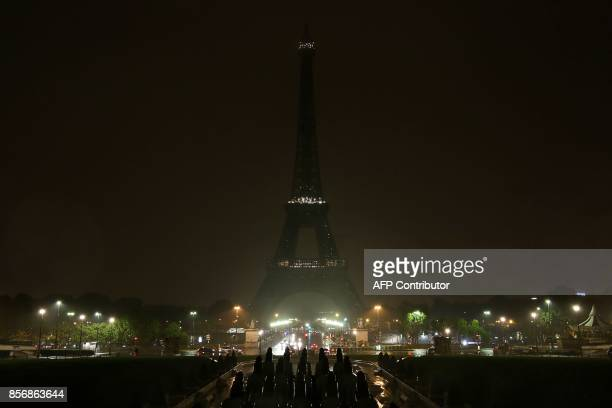 The lights of the Eiffel Tower in Paris are switched off on October 2 2017 in tribute to the victims of the attacks in Las Vegas and Marseille At...
