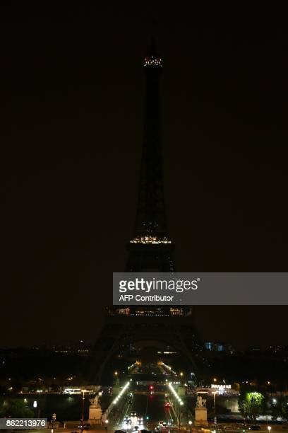 The lights of the Eiffel Tower in the French capital Paris are switched off on October 16 in homage to the victims of an attack two days ago in the...