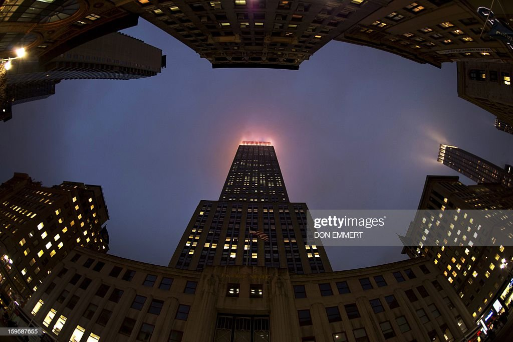 The lights of the Empire State Building illuminate the fog January 16, 2013 in New York. During 2012, the building's metal halide lamps and floodlights were replaced with LED fixtures, increasing the available colors from nine to over 16 million. AFP PHOTO/DON EMMERT
