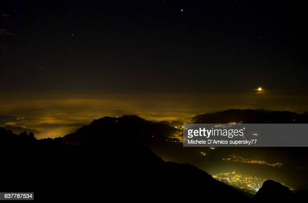 The lights of the Po plaine below a fog layer from the the top of a mountain