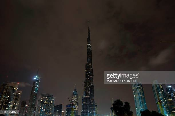 The lights on the Burj Khalifa tower are switched off for an hour in Downtown Dubai on March 25 as iconic landmarks and skylines are plunged into...