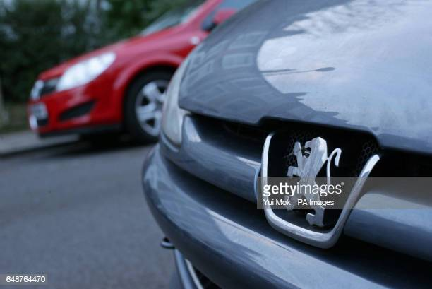 The lion emblem on the front grille of a Peugeot car with a Vauxhall car parked in the background in London French car giant PSA Group has sought to...