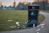 The litter bin in public park and litter around .