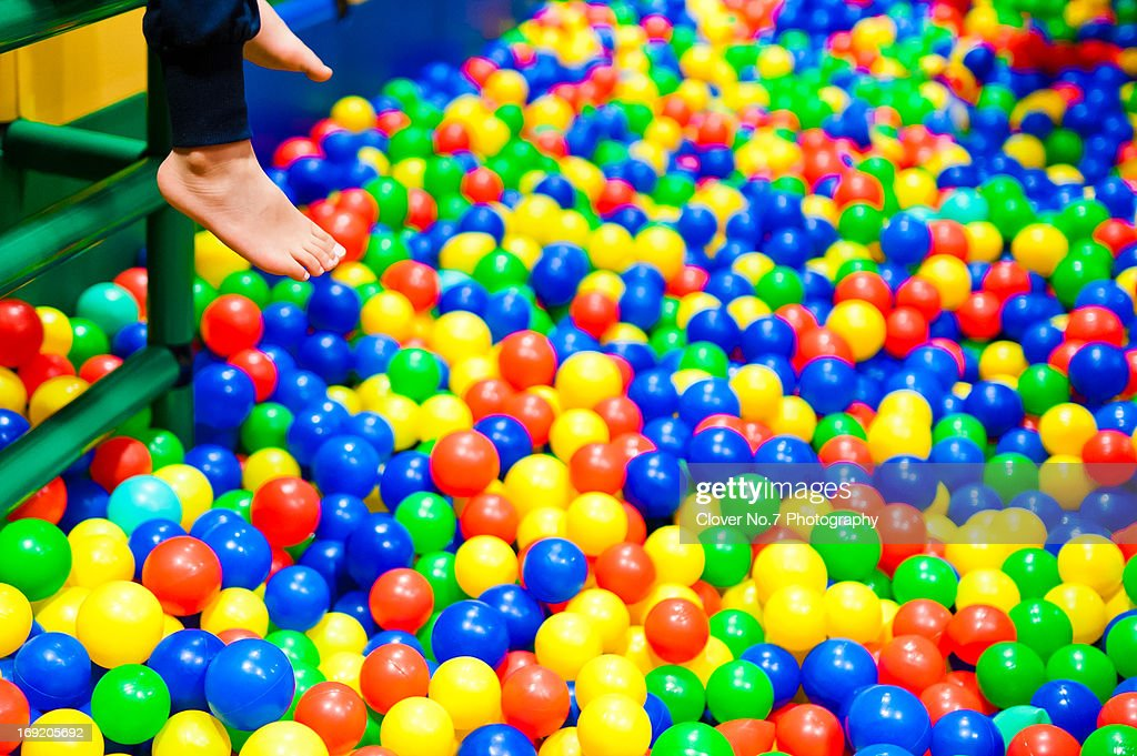 The little boy in color balls pool play. : Stock Photo