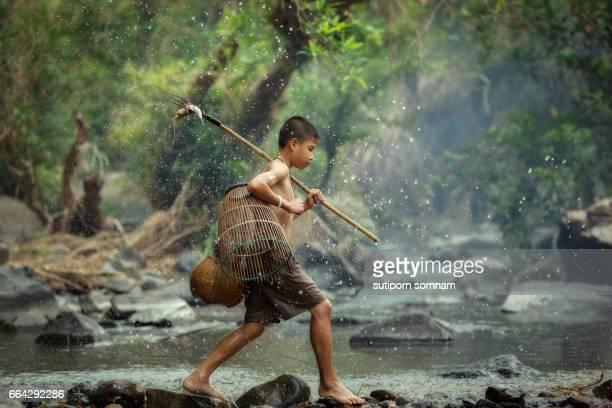 The Little fisherman boy walking in the creek