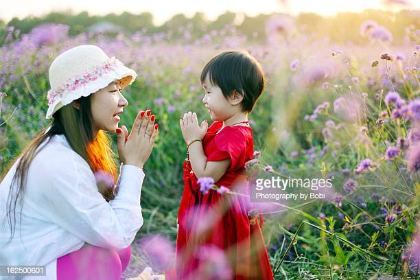 The little girl and her mother playing in flowers