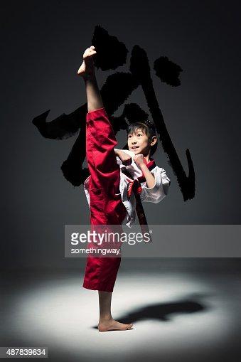The little girl is practising Taekwondo.