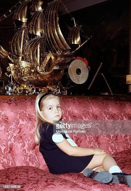 The little Infanta Elena daughter of the princes of Spain Juan Carlos and Sophia seats peaceably on a purple velvet sofa next to a big gilted galleon...