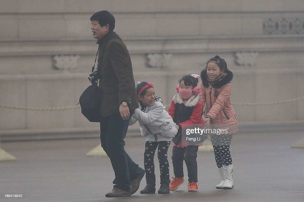 The little tourists play on the ground with frozen ice at the Tiananmen Square during severe pollution on January 31, 2013 in Beijing, China. Heavy smog that has choked Beijing for the last five days weakened slightly on Thursday due to a light rainfall, although the capital's air remains heavily polluted. The haze choking many Chinese cities covers a total area of 1.43 million square kilometers, the China's Ministry of Environmental Protection said Wednesday.