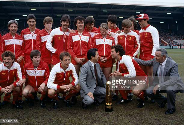 The Liverpool team pose with the Canon First Division Championship trophy and Canon Managing Director Mr Yamashita prior to their match against...