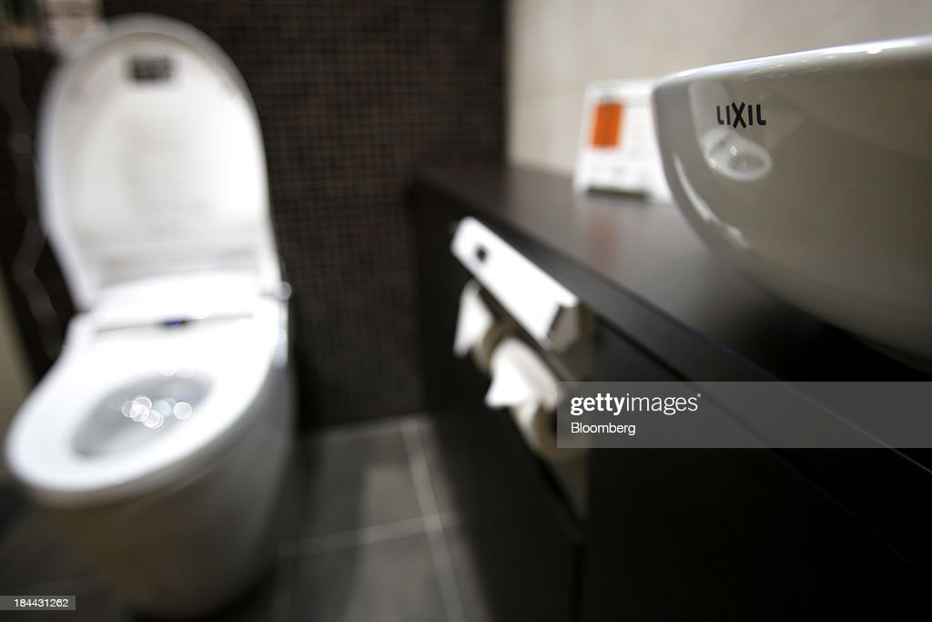 The Lixil Group Corp. logo is seen on a wash basin as a Satis toilet stands on display at the company's showroom in Tokyo, Japan, on Friday, Oct. 11, 2013. Lixil and Development Bank of Japan agreed on Sept. 26 to buy bathroom-fixtures maker Grohe Group, valuing the German company at 3.06 billion euros ($4.1 billion). Photographer: Kiyoshi Ota/Bloomberg via Getty Images