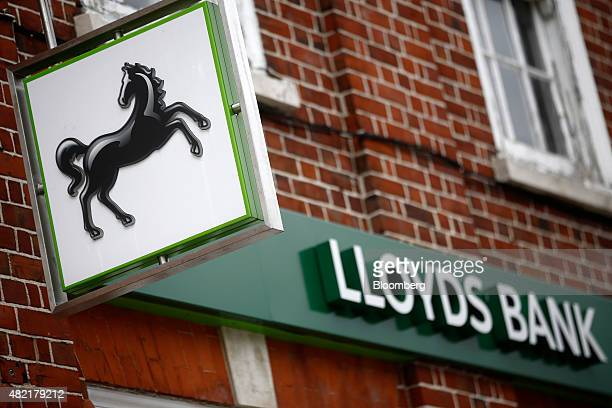 The Lloyds' prancing horse logo sits on a sign as it hangs outside a Lloyds Bank branch a unit of Lloyds Banking Group Plc in London UK on Monday...