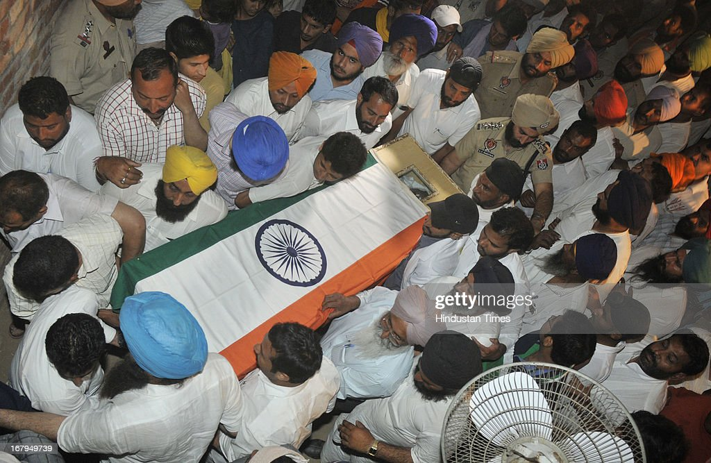 The local residents of the native village of Indian prisoner Sarabjit Singh carries his coffin covered in Indian National Flag at his native house in Bikhiwind on May 2, 2013 about 40 Kms from Amritsar, India. Sarabjit Singh, an Indian prisoner in Pakistan died after being brutally assaulted in a Pakistani jail. Meanwhile, a second autopsy was conducted on Thursday night by a team of six doctors at the government-run Amritsar Medical College to ascertain the cause of Sarabjit's death. The first postmortem was carried out at the Jinnah Hospital in Lahore.