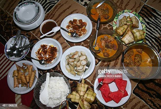 The local specialty of chicken curry eggs in sauce and rice wrapped and cooked in coconut leaves called 'ketupat' and watermelon are prepared for the...