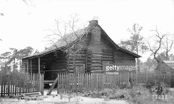 The log cabin of Mrs MA Hamilton in Walton County Florida in 1909 There is a split picket fence around the house This cabin is nicer than many of its...
