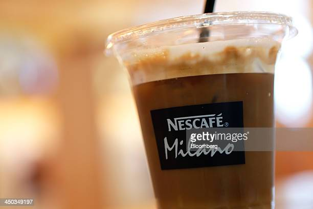 The logo for Nestle SA's Nescafe coffee is seen on a cup of iced latte in this arranged photograph at the company's Cafe Nescafe coffee shop in the...
