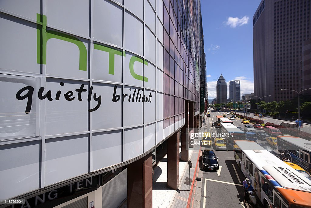 The logo for Taiwan's leading smartphone maker HTC (L) is pictured above a busy street in Taipei on July 20, 2012. Taiwan's leading smartphone maker HTC said on July 19 it was suing technology giant Apple in the United States, claiming it has infringed on its patents. AFP PHOTO / Sam YEH