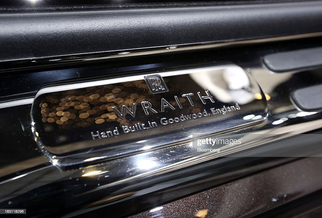 The logo for the Rolls-Royce Wraith automobile, produced by Rolls-Royce Motor Cars Ltd., is displayed inside the vehicle as it sits on the company's stand ahead of the opening day of the 83rd Geneva International Motor Show in Geneva, Switzerland, on Monday, March 4, 2013. This year's show opens to the public on Mar. 7, and is set to feature more than 100 product premiers from the world's automobile manufacturers. Photographer: Chris Ratcliffe/Bloomberg via Getty Images