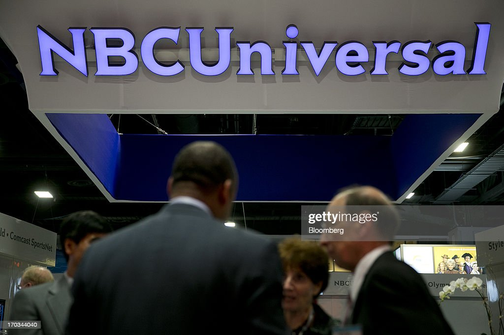 The logo of Comcast Corp.'s NBCUniversal Media LLC is seen on the exhibit floor during the National Cable and Telecommunications Association (NCTA) Cable Show in Washington, D.C., U.S., on Tuesday, June 11, 2013. The Cable Show is expected to bring in more than 10,000 attendees with 286 companies on the exhibit floor. Photographer: Andrew Harrer/Bloomberg via Getty Images