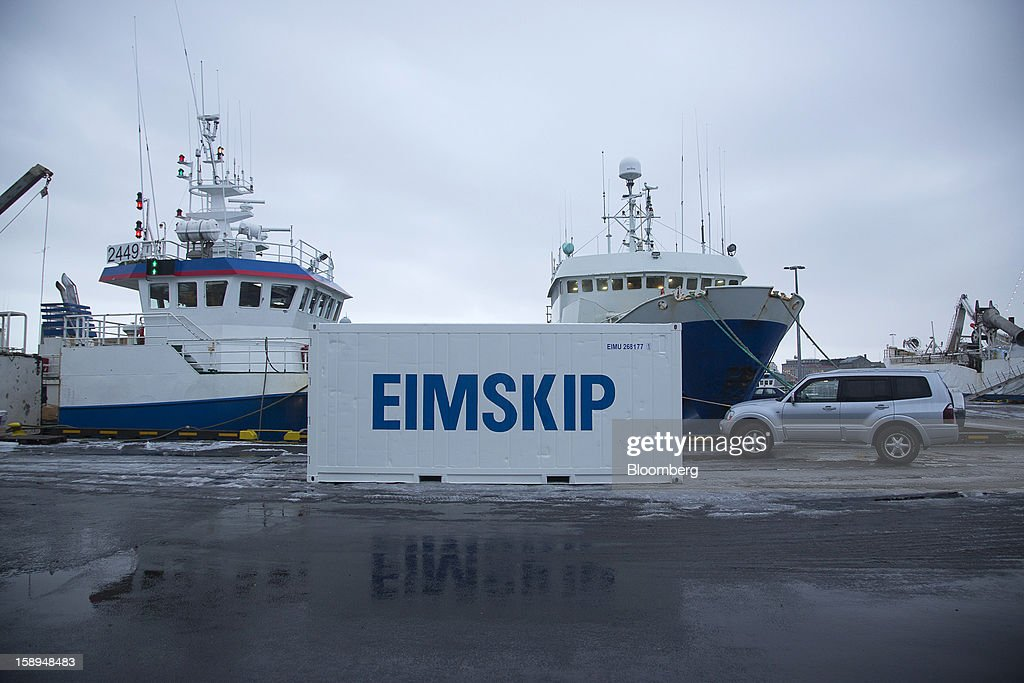 The logo of Eimskipafelag Island hf, or Eimskip, shipping and storage company sits on a container next to commercial fishing vessels at the harbor in Reykjavik, Iceland, on Wednesday, Jan. 2, 2013. Creditors of Iceland's three biggest failed banks are fighting for a waiver to krona controls imposed in 2008 amid risks pay-outs will be delayed beyond 2015. Photographer: Arnaldur Halldorsson/Bloomberg via Getty Images
