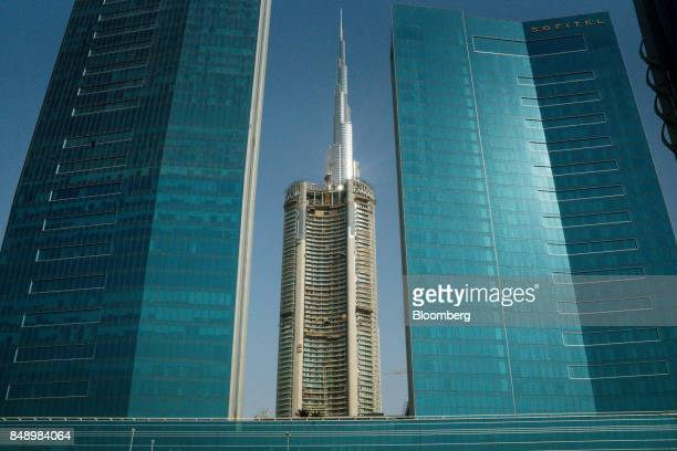 The logo of Emaar Properties PJSC center stands above a tower under construction beyond the Sofitel hotel operated by Accor Hotels and the Burj...