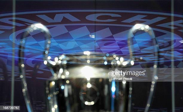The logo of FC Bayern Muenchen is reflected in the showcase of the UEFA Champions League trophy in the FC Bayern Erlebniswelt during the UEFA...