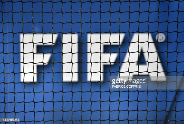 The logo of FIFA is seen through a net on October 13 2016 at the world football's governing body headquarters in Zurich FIFA president Gianni...