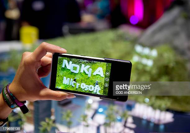 The logo of Finnish mobile manufacturer 'Nokia' and US multinational software company 'Microsoft' are seen on the display of the Lumia 1020 Windows...