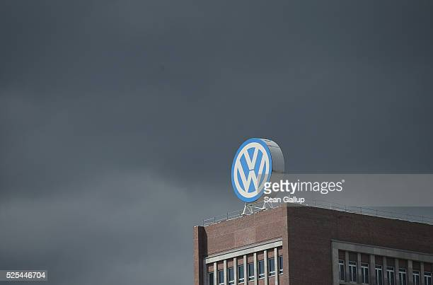 The logo of German automaker Volkswagen AG stands on an administrative building at the Volkswagen factory as a dark cloud passes behind on the day of...