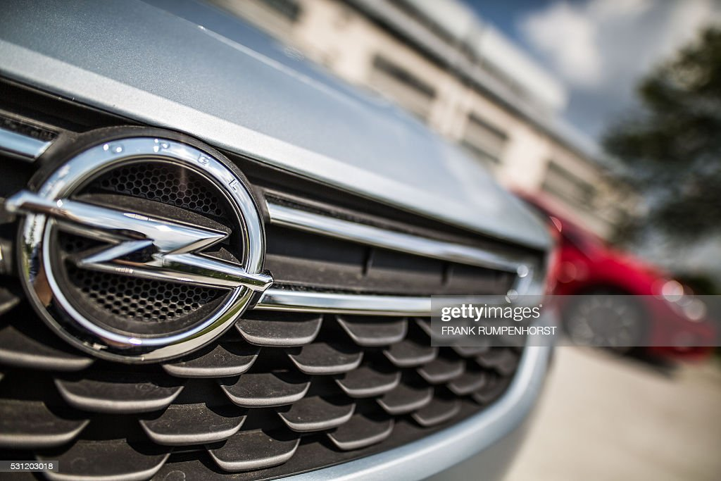 The logo of German car maker Opel can be seen on a car standing in front of the company's plant in Ruesselsheim western Germany on May 13 2016 Opel...