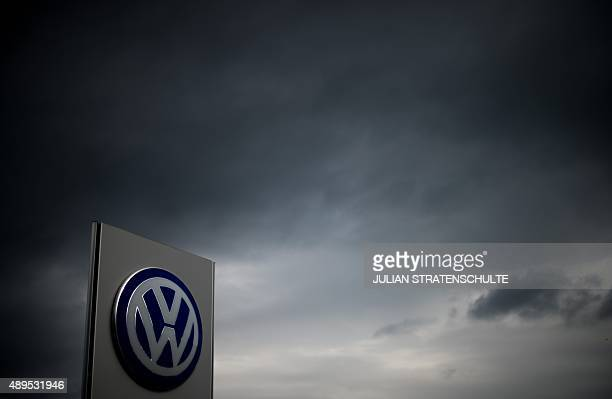 The logo of German car maker Volkswagen can be seen as dark clouds hang in the sky over a Volkswagen trader in Hanover central Germany on September...