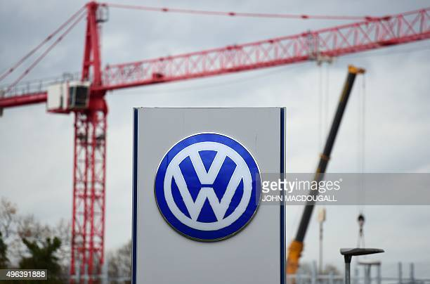 The logo of German car maker Volkswagen is seen near a cranes of a construction site in Wolfsburg on November 9 2015 VW is engulfed in a massive...