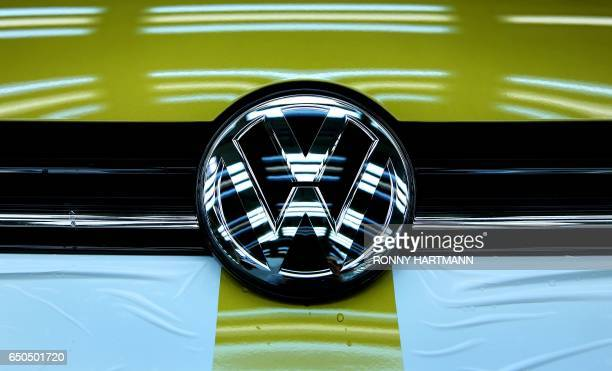 The logo of German car maker Volkswagen is seen on a Golf VII car at an assembly line at VW plant in Wolfsburg central Germany on March 9 2017 / AFP...