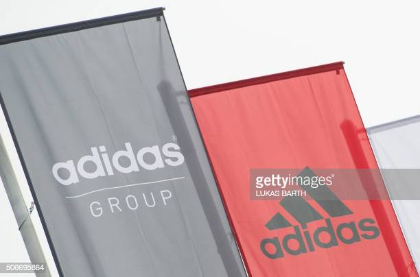 The logo of German sport brand Adidas is pictured on waving flags in front of the Adidas Headquarter in Herzogenaurach on January 25 2016 / AFP /...