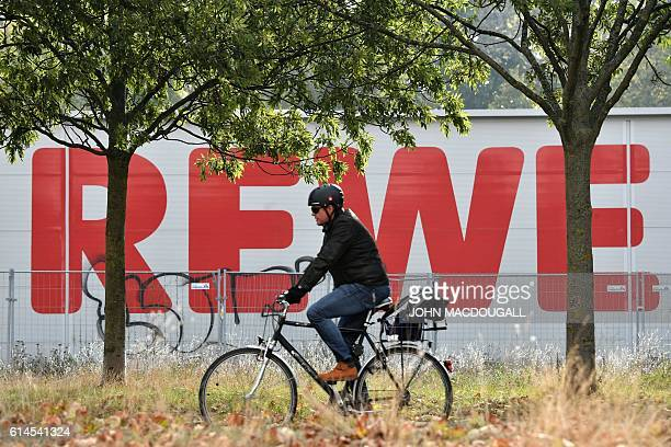 The logo of German supermarket chain Rewe is seen in the background as a man rides a bicycle on October 14 2016 in Berlin After negociation talks...