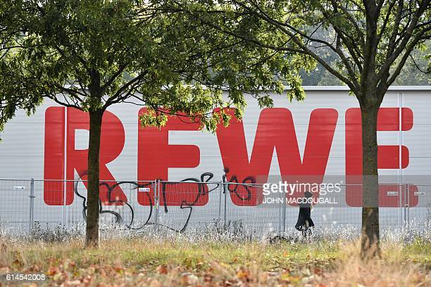 The logo of German supermarket chain Rewe is seen in the background as a woman passes by on October 14 2016 in Berlin After negociation talks between...