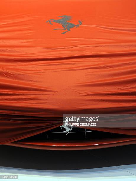 The logo of Italian carmaker Ferrari is seen on a car that waits to be unveiled on March 1 2010 during the first press day at the 80th Geneva...