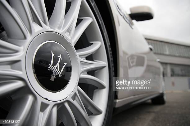 The logo of Italian luxury car manufacturer Maserati is seen on the front wheel of a Maserati Quattroporte outside a Maserati plant on May 22 2014 in...