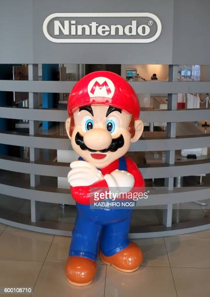 The logo of Japanese gaming giant Nintendo and its game character Super Mario are displayed at a show room in Tokyo on September 8 2016 Tokyo stocks...