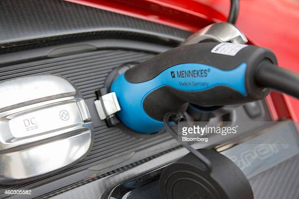 The logo of Mennekes Elektrotechnik GmbH sits above the words 'Made in Germany' on a electric charging plug connected to an Audi R8 etron hybrid...
