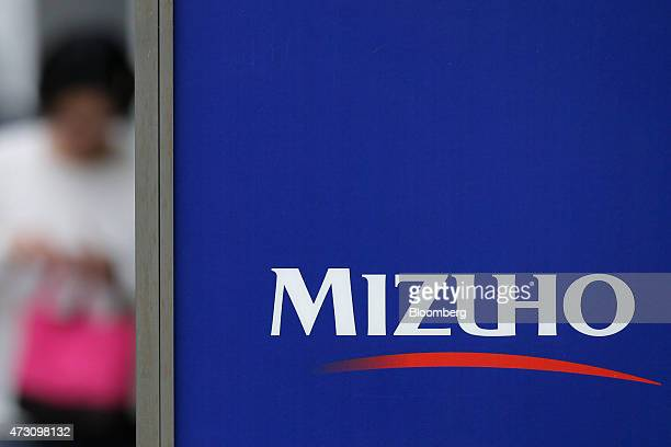 The logo of Mizuho Financial Group Inc is displayed on signage outside a Mizuho Bank Ltd branch in Tokyo Japan on Tuesday May 12 2015 Mizuho...
