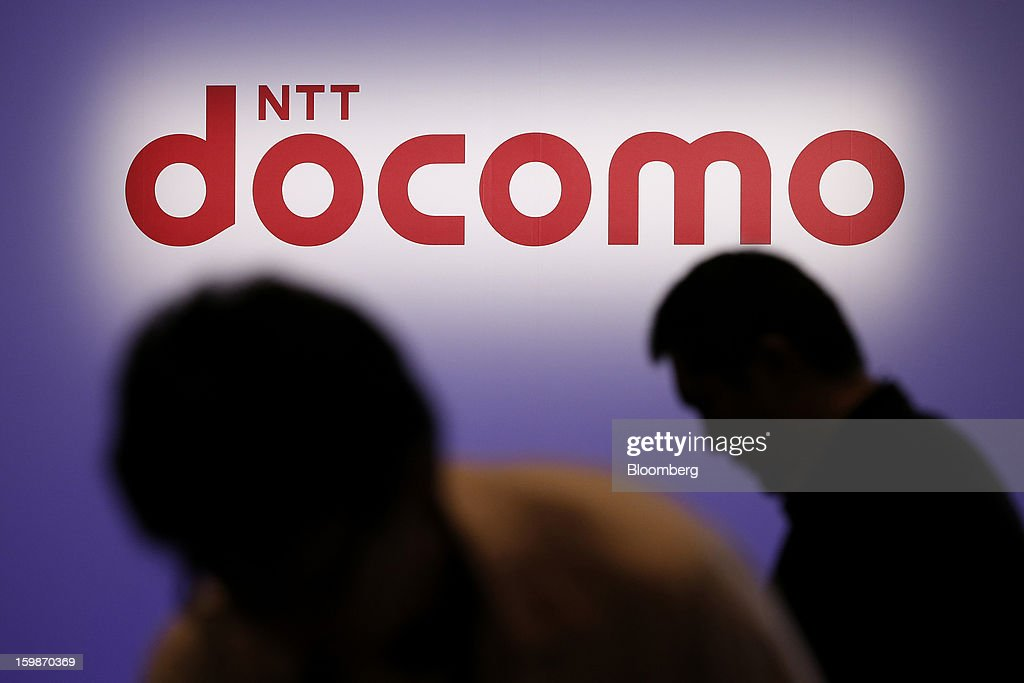 The logo of NTT DoCoMo Inc. is seen beyond visitors during the company's product launch in Tokyo, Japan, on Tuesday, Jan. 22, 2013. NTT DoCoMo, Japan's biggest mobile-phone company, released their latest tablet and smartphone series today. Photographer: Kiyoshi Ota/Bloomberg via Getty Images