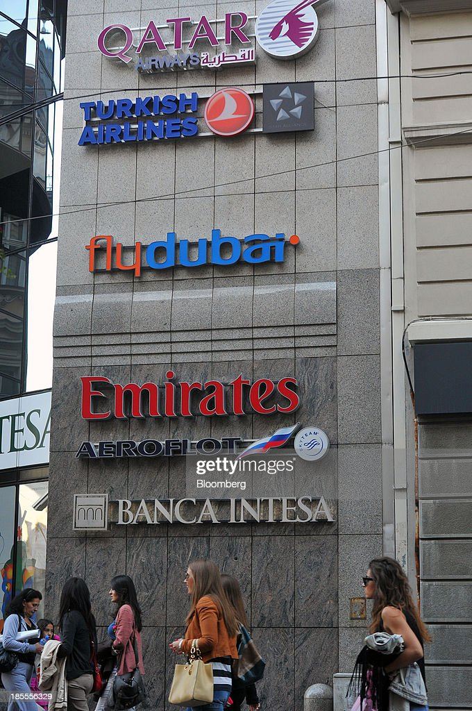 The logo of Qatar Airways Ltd. is displayed on a wall of a building above signs for Turkish Airlines, the budget carrier FlyDubai, Emirates Airline, OAO Aeroflot and Banka Intesa SpA as shoppers pass in Belgrade, Serbia, on Sunday, Oct. 20, 2013. Serbia's government revealed a salvo of measures to bring the public finance deficit and debt back under control by 2017 after the head of the largest coalition party warned the country was on the brink of insolvency. Photographer: Oliver Bunic/Bloomberg via Getty Images