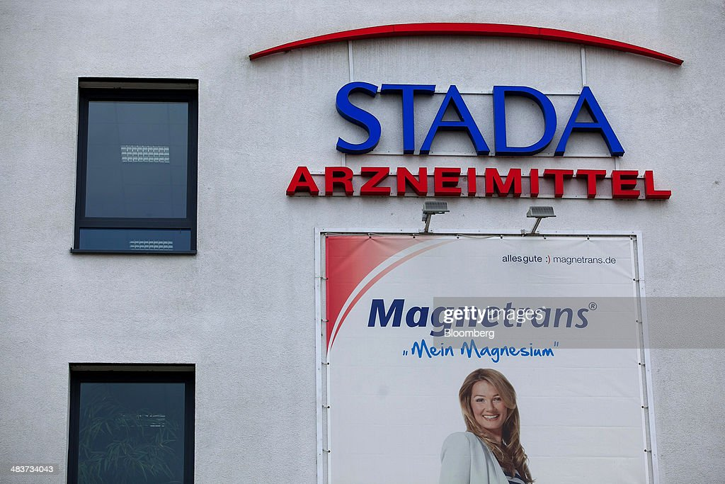 The logo of Stada Arzneimittel AG sits above an advertising hoarding for Magnetrans magnesium supplements outside factory of Germany's biggest maker of generic drugs, in Bad Vilbel, Germany, on Wednesday, April 9, 2014. Last month Stada Arzneimittel AG climbed 2.7 percent after Deutsche Bank AG upgraded its rating on the maker of generic drugs. Photographer: Krisztian Bocsi/Bloomberg via Getty Images