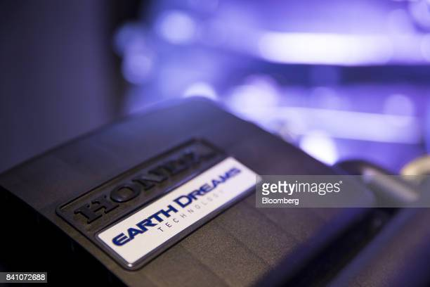 The logo of the Earth Dreams powertrain technology is displayed on the engine of a Honda Motor Co NBox minicar during a media preview in Tokyo Japan...