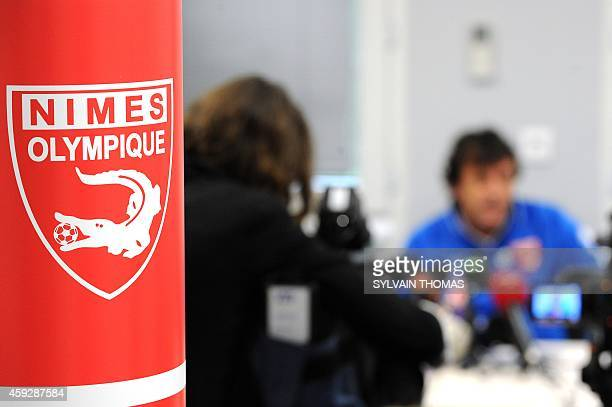 The logo of the French L2 football club Nimes Olympique is pictured as Nimes Olympique coach Jose Pasqualetti speaks during a press conference after...
