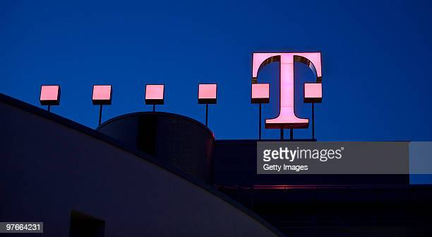The logo of the German telecoms provider Deutsche Telekom is pictured at twilight at the company's headquarters on March 09 2010 in Bonn Germany
