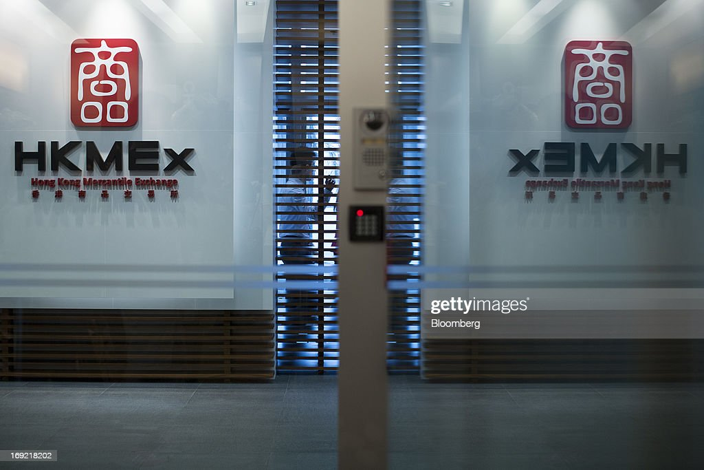 The logo of the Hong Kong Mercantile Exchange Ltd. (HKMEx) is reflected in a glass panel at the company's offices in Hong Kong, China, on Wednesday, May 22, 2013. Police began probing the Hong Kong Mercantile Exchange, the failed commodities market set up by a member of the city's cabinet, after the securities regulator said it found suspected financial irregularities. Photographer: Jerome Favre/Bloomberg via Getty Images