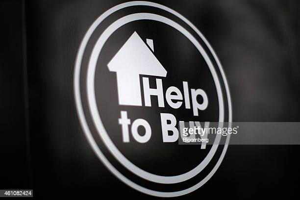 The logo of the UK Government's 'Help to Buy' scheme stands on a sign outside newly built houses in Tonbridge UK on Tuesday Jan 6 2015 Demand for UK...
