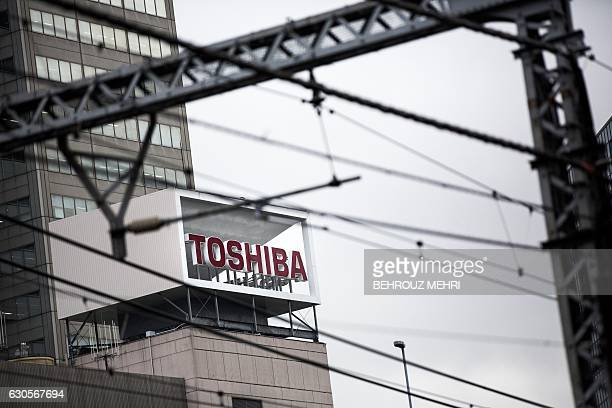 The logo of Toshiba Corporation is displayed at the company's headquarters in Tokyo on December 27 2016 Shares in Toshiba dived nearly 12 percent on...